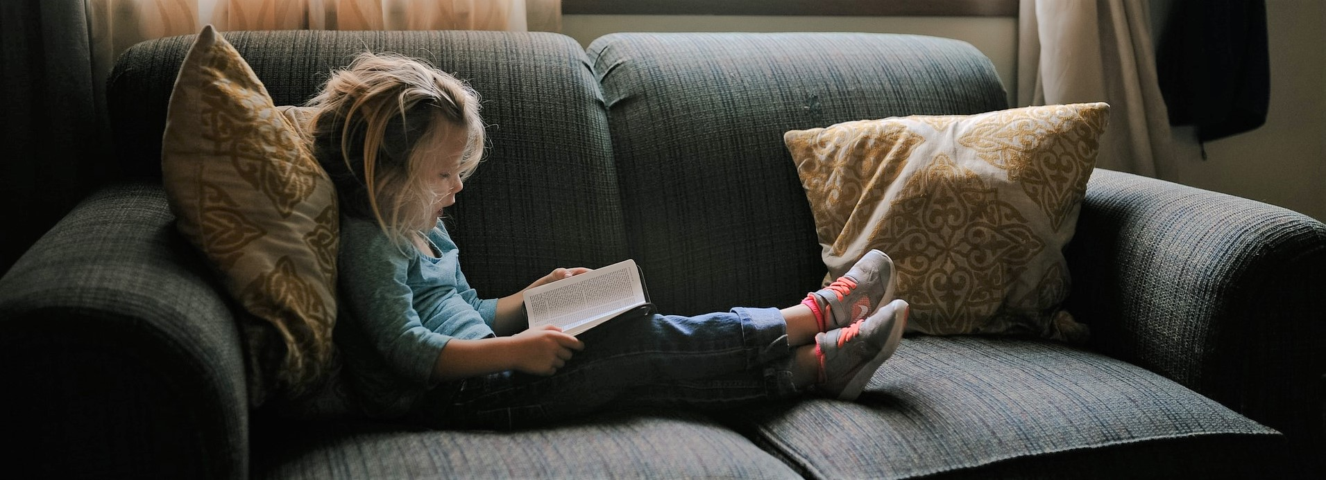 Little Girl Reading on a couch in Nebraska | Kids Car Donations