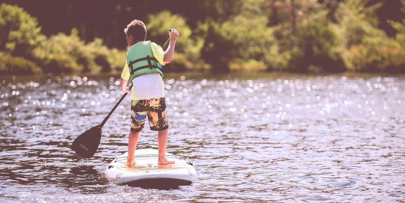Kid Paddleboarding on a Lake   Kids Car Donations