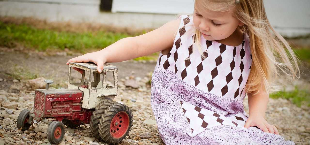 Little Girl Playing with a Tractor Toy | Kids Car Donations