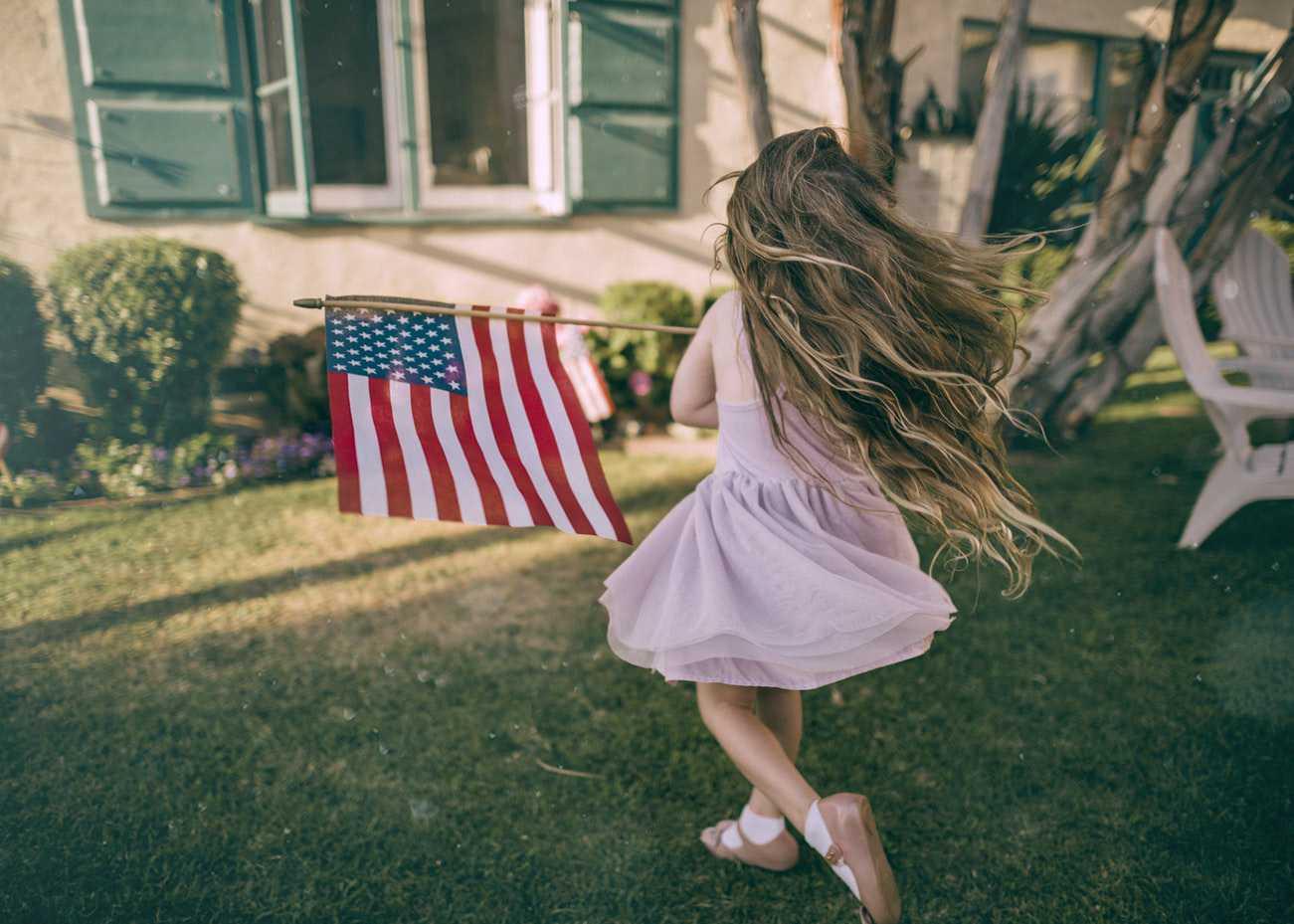 Little Girl Holding the American Flag | Kids Car Donations